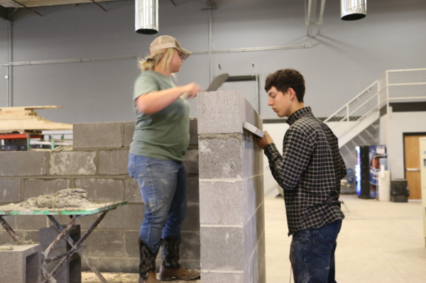 Two masonry students working together to build a wall.