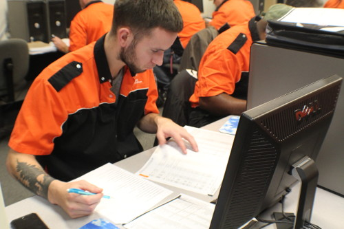 A Harley-Davidson student doing paper work in a computer lab.