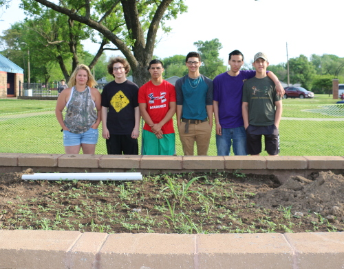 Masonry students proudly standing next to a raised garden bed that they built.