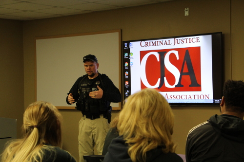 A police officer guest-speaking in the Criminal Justice classroom.