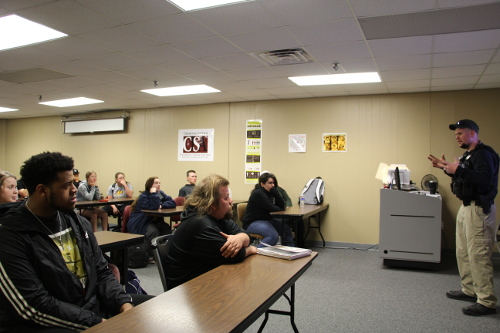 Criminal Justice students listening to a police officer give a presentation.