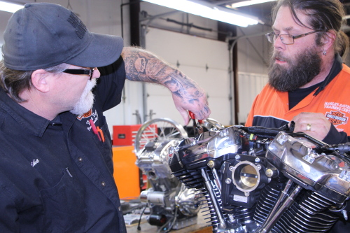 Two Harley-Davidson technicians working on a bike engine.