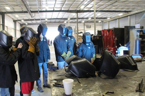 Several students look on as an instructor demonstrates welding technique.