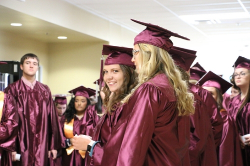 a group of students standing around in graduation gowns and caps