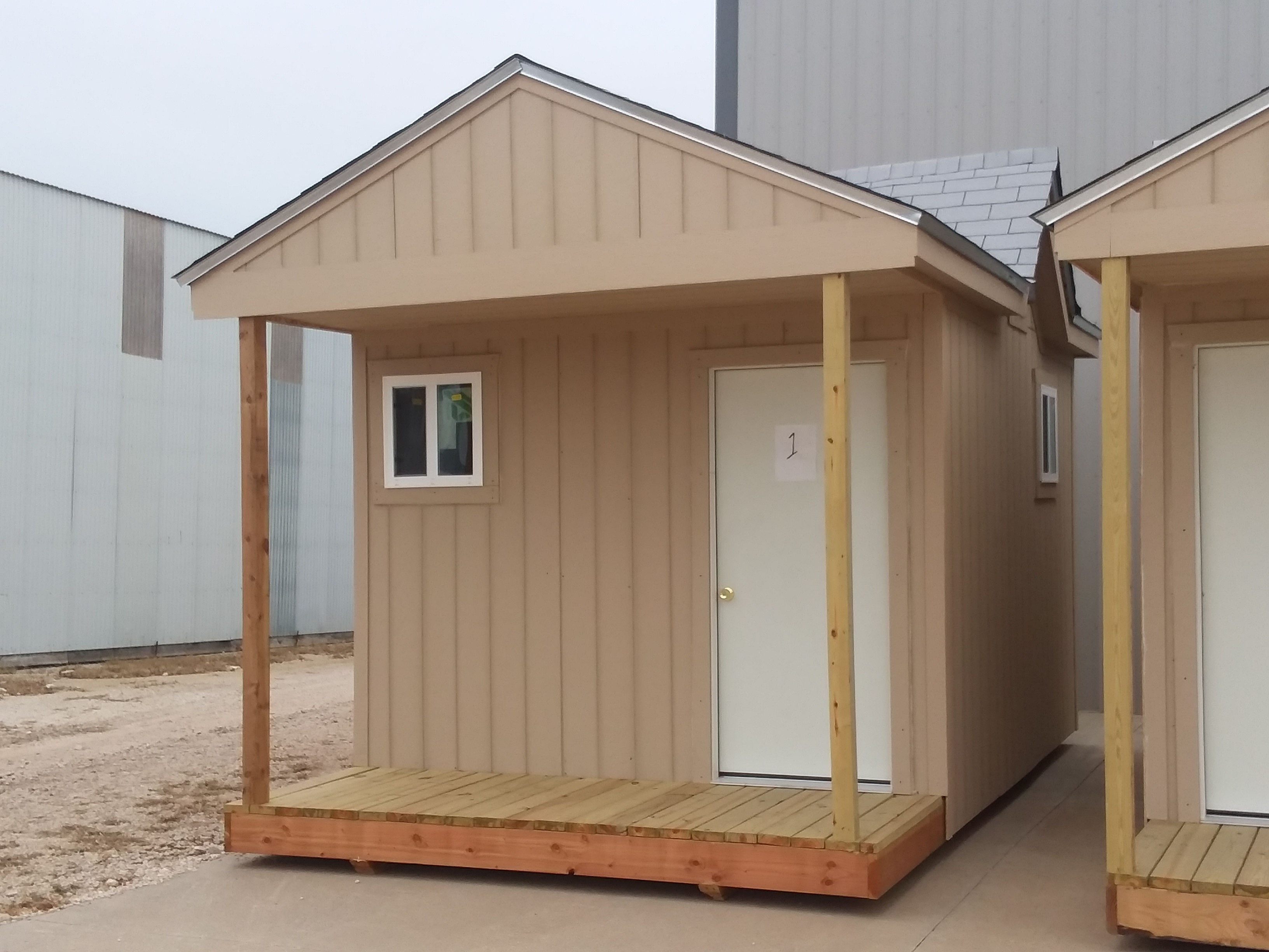 A cabin with a window and door on its front face, a small porch, and the number 1 on the door.