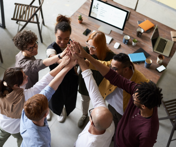 """downward facing photo of a diverse group of people """"high-fiving"""" after a group project"""
