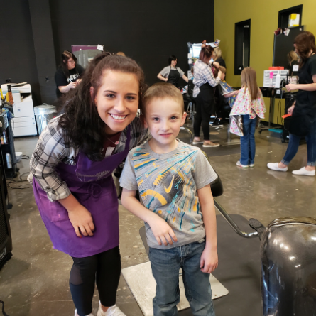 cosmetology student standing with a young boy after his hair cut