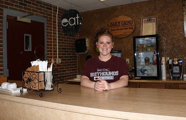 A Daily Grind worker standing behind the counter, with her hands together in front of her, smiling at the camera.