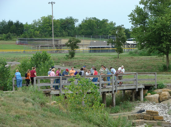 A dozen or so people on a wooden bridge observing the water that runs below.
