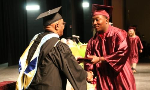 a student receiving his diploma at graduation