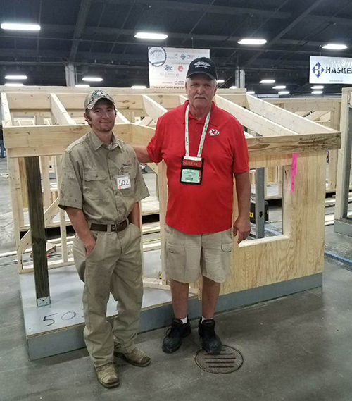 A carpentry student and his instructor standing together in front of a mini house that the student made for a carpentry competition