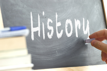 "A person writing the word ""history"" on a blackboard."