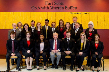 Business students posing with Warren Buffett at the Fort Scott Q&A with Warren Buffett event.