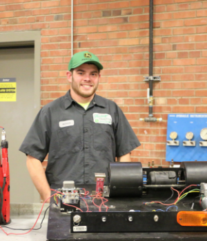 John Deere student standing with some equipment