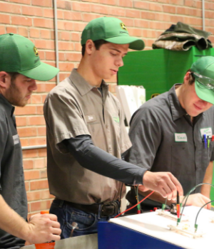 three John Deere students demonstrating some electrical equipment