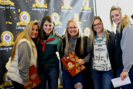 five girls standing in front of the FSCC centennial banner