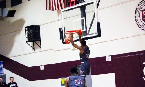picture of a FSCC men's basketball player dunking the basketball