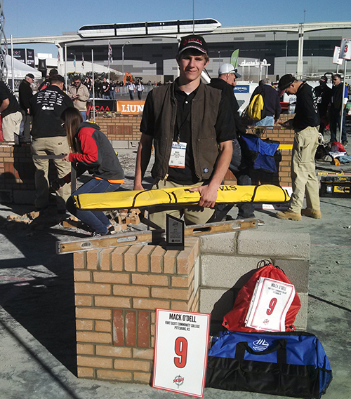 A photo of Mack O'Dell, a masonry student at FSCC, standing next his entry in a masonry competition that he won 9th place in.