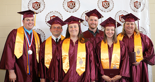 Six graduates from Miami County posing for the camera in their graduation robes.