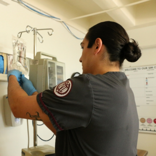 A nursing student adjusting the IV machine during simulation lab