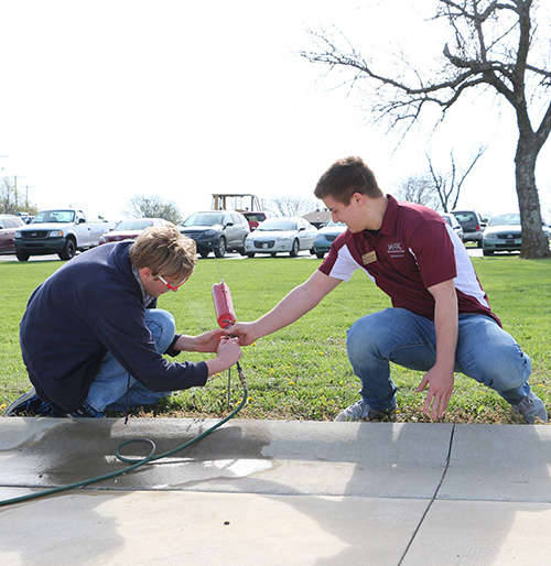 A STEM club student and a president's ambassador performing an experiment with a plastic bottle and a hose.