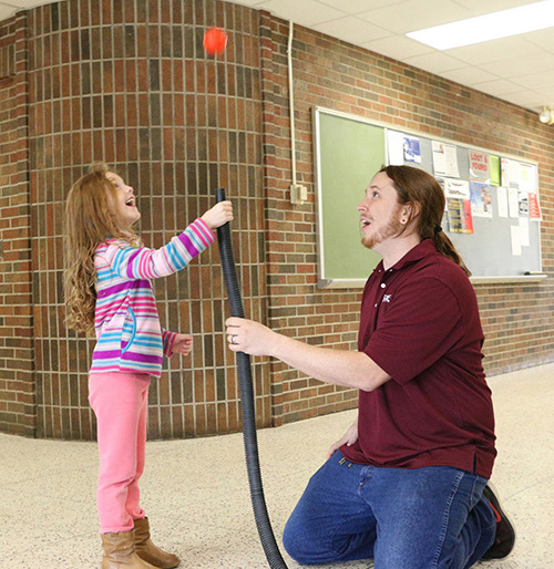 A STEM club student helping a child keep a plastic ball in the air by blowing air up from under it.
