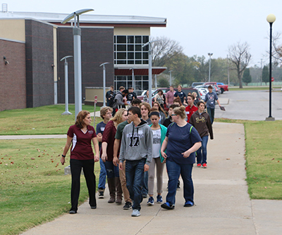 High school seniors walking down the sidewalk on a guided tour of the Fort Scott campus during Senior Day.