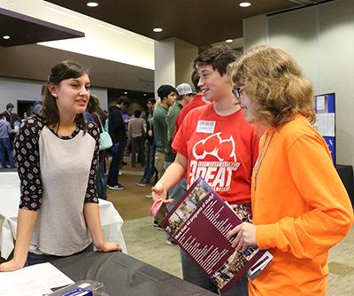 Two high school students and one college student standing around an information table while talking about the college during Senior Day.