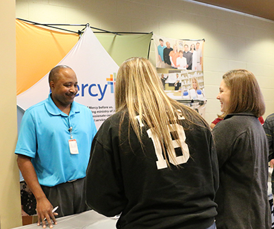 Two people getting information about Mercy Hospital from a man behind an information table during Senior Day.