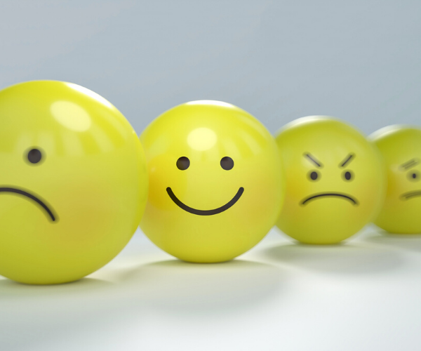 a line of emoji yellow balls with a sad face in the front, then a happy face, then a faded mad face, and half of a crying face