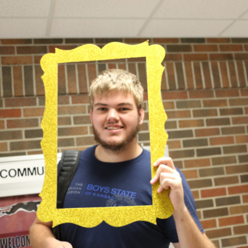 student posing for the camera with a gold frame around his face