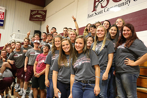 A large crowd of students cheering and smiling at the camera while at a basketball game.