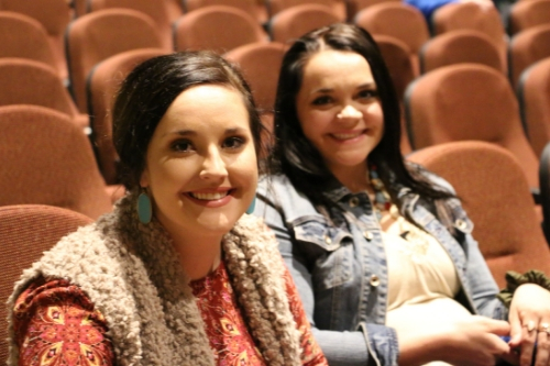 two female students smiling for the camera sitting in the auditorium