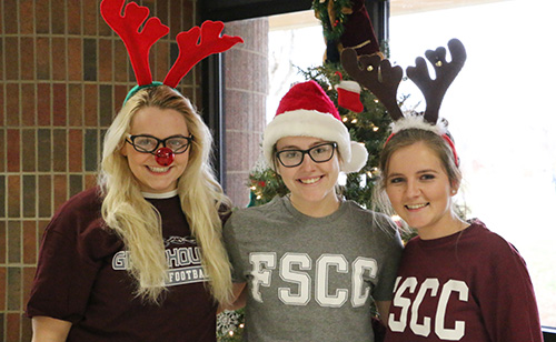 Three students from the President's Ambassadors organization smiling and wearing Christmas-themed hats.