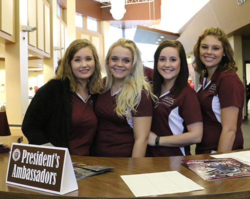 Four President's Ambassadors smiling for the camera as they get ready for an event.