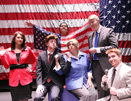 The main student actors and actresses of the Bald Soprano play posing in front of a large American flag.