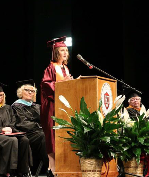 Cara Comstock standing behind a podium and giving a speech at her graduation.