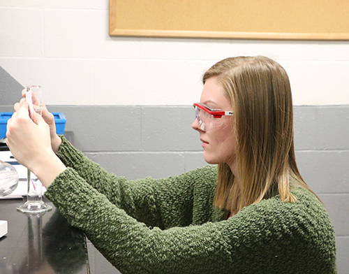 A student examining a vial in Chemistry class.