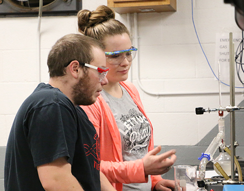 A male and female student working together at a chemistry station.