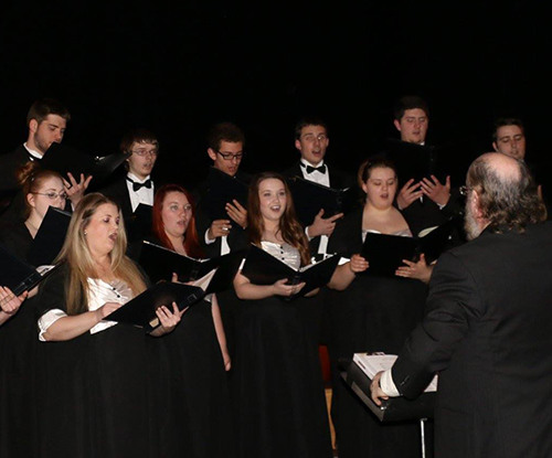 FSCC's choir and the choir's conductor performing on stage.
