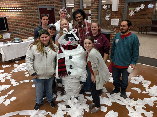 Several members of Christians on Campus posing next to a snowman they made out of toilet paper.