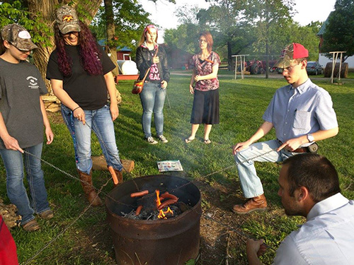 Several members of Christians on Campus roasting hot dogs over a fire pit at Larry Shead's farm.