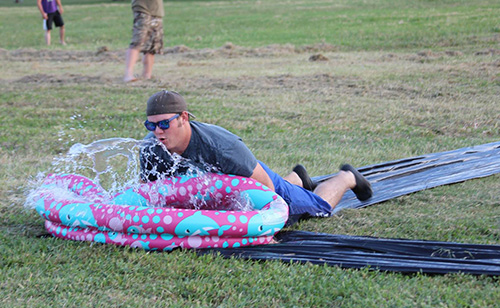 A student sliding down a slip-n-slide and landing in a kiddie pool at the end.