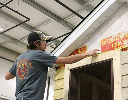 A Construction Trades student measuring the outside of a small building.