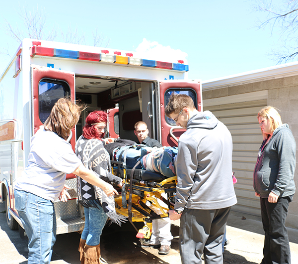 EMT students being trained on how to place someone who's on a gurney in an ambulance.