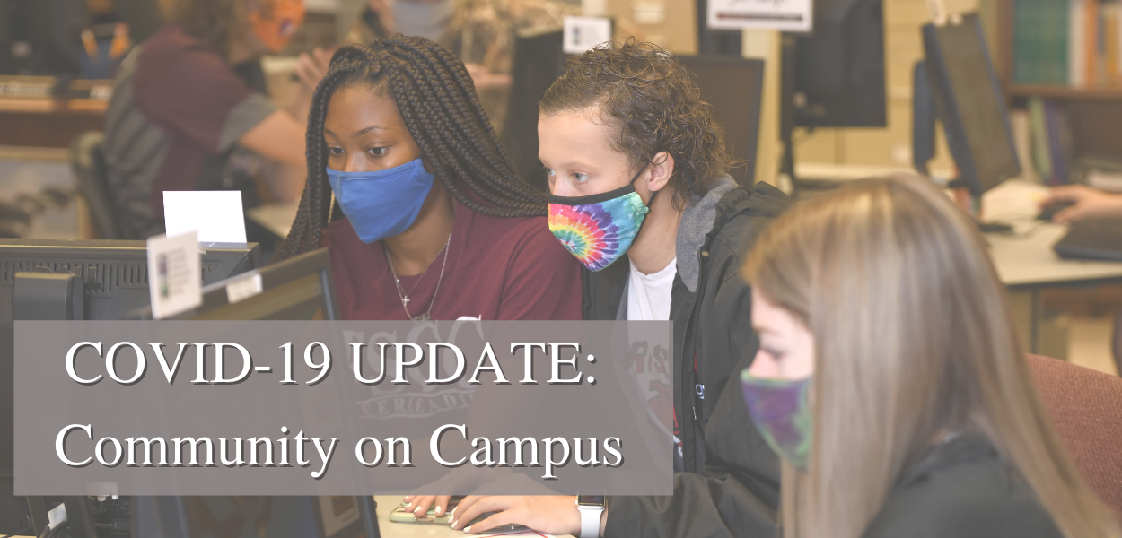 "students with masks on looking at a computer with ""COVID-19 Update: Community on Campus"" written in the bottom left corner"