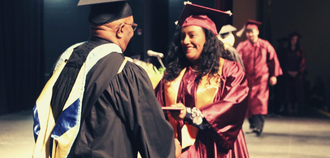 picture of a student shaking hands with a board member at graduation 2018