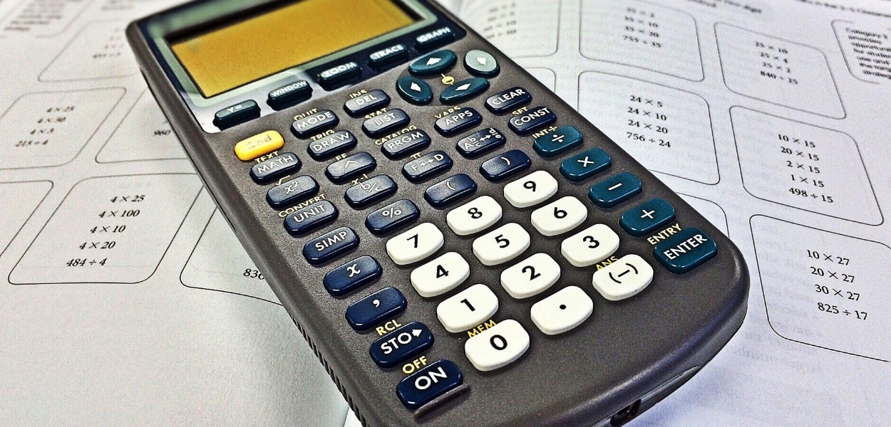 picture of a math book with a calculator on top