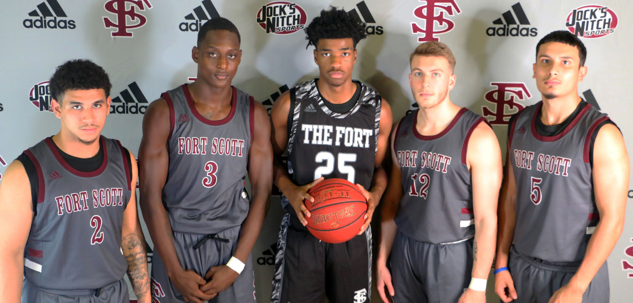 a group picture of men's basketball posing for the camera in their jerseys holding a basketball