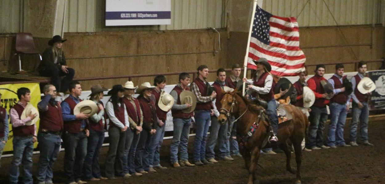 rodeo team standing in a line with hats removed saluting the American flag